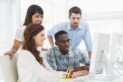 一起使用计算机的被集中的工友 免版税库存图片