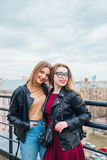一起俏丽的妇女夫妇在都市风景 屋顶的两个快乐的美丽的女孩 美好的城市视图 免版税库存照片