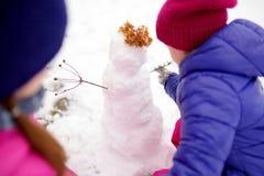 一起修造雪人的两个可爱的小女孩在美丽的冬天公园 使用在雪的逗人喜爱的姐妹 免版税图库摄影