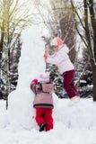 一起修造雪人的两个滑稽的可爱的妹  库存图片