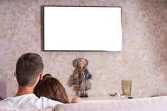 一起偎依在沙发和观看的电视的夫妇 免版税库存图片