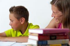 一起做家庭作业教训的母亲和儿子 免版税库存照片