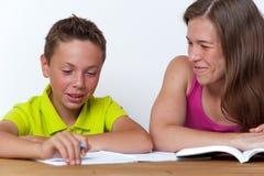 一起做家庭作业教训的母亲和儿子 图库摄影