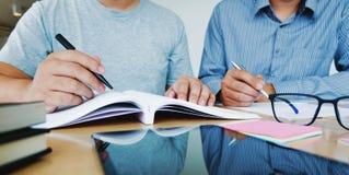 一起做家庭作业的两名确信的学生,当坐在家庭地方时 库存图片