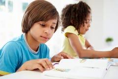 一起做家庭作业的孩子在厨房里 免版税库存图片