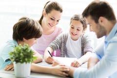 一起做家庭作业的家庭在桌上 库存照片