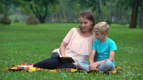 一起做家庭作业的母亲和儿子在公园,儿童教育,父母身分 股票视频