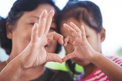 一起做心形用手的亚裔祖母和小孩女孩 库存照片