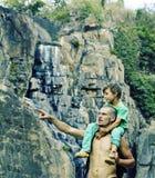 一起做旅行的父亲和儿子对瀑布,幸福家庭在度假,自然地方 库存图片