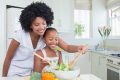 一起做沙拉的母亲和女儿 免版税库存照片
