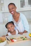 一起做沙拉的画象母亲和女儿 库存照片