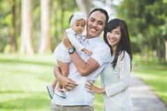 一起做父母与他们逗人喜爱的婴孩在获得的公园乐趣 免版税库存图片