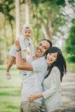 一起做父母与他们逗人喜爱的婴孩在获得的公园乐趣 库存图片