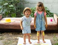 一起做艺术和工艺的愉快的孩子 愉快地微笑可爱的女孩和的男孩画象,当享受艺术和工艺时 免版税库存图片