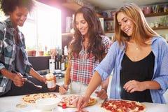 一起做薄饼的三个女性朋友在厨房里 免版税库存图片