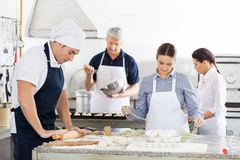 一起做面团的厨师在厨房里 免版税图库摄影