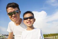 一起做鬼脸的父亲和儿子在公园 库存照片