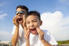 一起做鬼脸的父亲和儿子在公园 库存图片