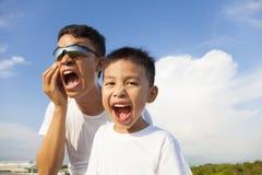 一起做鬼脸的父亲和儿子在公园 免版税库存图片