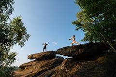 一起做锻炼的健身教练员黑人和白种人妇女混合的族种夫妇在岩石峰顶 体育运动 免版税库存照片