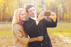一起做selfie的愉快的微笑的年轻夫妇画象在智能手机 图库摄影