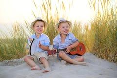 一起儿童游戏音乐在海滩 免版税库存照片