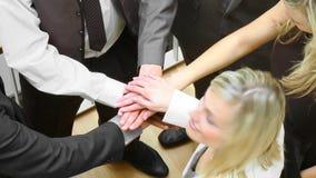 一起关闭企业队用手和微笑对照相机的白肤金发的女实业家 股票录像