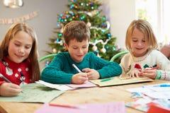 一起写信的三个孩子给圣诞老人 库存图片