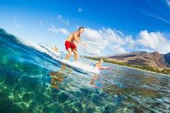一起冲浪的父亲和的儿子,乘坐的波浪 库存图片