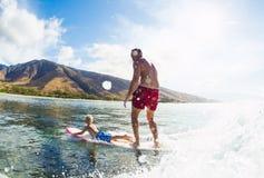 一起冲浪的父亲和的儿子,乘坐的波浪 免版税库存照片