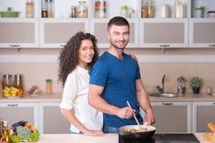 一起准备晚饭的美好的夫妇  图库摄影