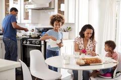 一起准备膳食的年轻非裔美国人的家庭在他们的厨房里 库存照片
