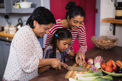 一起准备食物的多代的家庭在厨房里 图库摄影