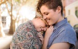 一起分享富感情的片刻的微笑的年轻女同性恋的夫妇外面 免版税库存图片