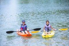 一起划皮船在湖的两个不同的男孩 免版税库存照片