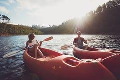 一起划皮船在湖的年轻夫妇 免版税图库摄影