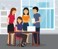 一起努力研究一台膝上型计算机的年轻企业队在办公室 免版税库存图片