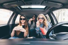 一起友谊和时间在路 获得乐趣一起吃快餐的三名年轻和秀丽妇女并且驾驶在旅行的一辆汽车 图库摄影