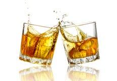 一起叮当响两块威士忌酒的玻璃,隔绝 免版税库存照片