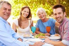 一起吃一对资深和一对年轻成人的夫妇户外 免版税库存照片
