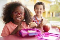 一起吃他们的被包装的午餐的两个年轻学校孩子 免版税库存图片