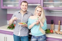 一起吃健康早餐的逗人喜爱的年轻夫妇 免版税库存照片