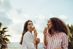 一起吃冰淇淋的妇女朋友 免版税库存照片