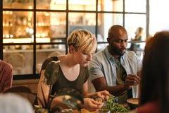 一起吃在一家时髦小餐馆的年轻朋友 免版税图库摄影