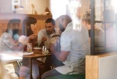 一起吃在小餐馆的不同的小组年轻朋友 库存图片