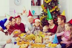 一起吃在欢乐圣诞晚餐期间的大家庭 免版税库存照片
