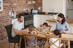 一起吃膳食的家庭在开放学制厨房里 库存照片