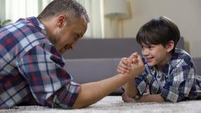 一起向他的武器角力的小男性孩子父亲挑战,获得乐趣 影视素材