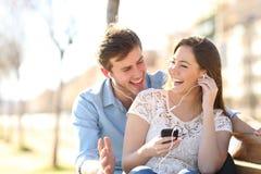 一起听到网上音乐的快乐的夫妇 免版税库存照片