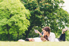 一起听到音乐的年轻亚裔可爱的夫妇或大学生在庭院里,有拷贝空间的 免版税库存图片